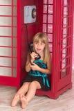 Flicka som kallar i rött en telefon Arkivfoton
