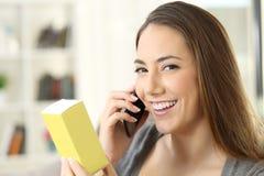 Flicka som kallar på telefonen som frågar information om en produkt Arkivfoto
