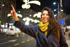 Flicka som kallar taxien i stads- miljö Arkivfoto