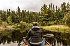 Flicka som kanotar med kanoten på sjön av två floder i algonquinnationalparken i Ontario Kanada på molnig dag arkivbilder