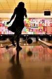 Flicka som kastar en bowlingklot arkivbild