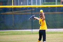 Flicka som kastar en softball Arkivfoto