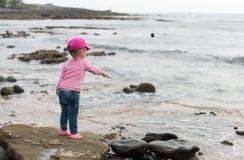 Flicka som kastar stenar in i havet Arkivfoto