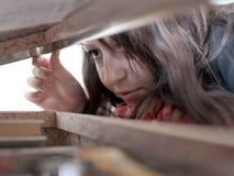Flicka som kikar in i en resväska Royaltyfri Foto