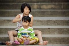 Flicka som klär hennes systers hår Arkivfoto