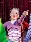Flicka som kläs som clownen Smiling och peka Arkivfoto