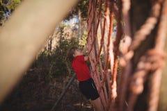 Flicka som klättrar ett netto under hinderkurs arkivfoto