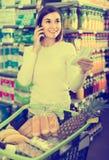 Flicka som konsulterar på telefonen om shopping i supermarket Royaltyfria Bilder