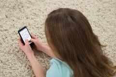Flicka som kontrollerar meddelandet på mobiltelefonen Fotografering för Bildbyråer
