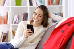 Flicka som kontrollerar smarta telefonmeddelanden i vinter arkivbilder