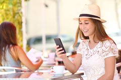 Flicka som kontrollerar telefonen bara i en coffee shop royaltyfria foton