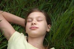 Flicka som kopplar av på en äng i natur Royaltyfri Bild