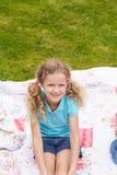 Flicka som kopplar av på filten under campa ferie royaltyfri bild