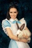 Flicka som kostymeras som Alice i underland med den vita kaninen Fotografering för Bildbyråer