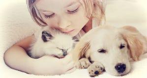Flicka som kramar affectionately kattungen och valpen arkivfoton