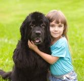 Flicka som kramar den Newfoundland hunden Arkivfoto
