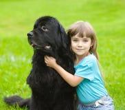 Flicka som kramar den Newfoundland hunden Arkivfoton