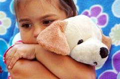 flicka som kramar den små valpen Arkivfoto