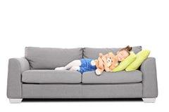 Flicka som kramar en nallebjörn och sover på soffan Royaltyfri Bild