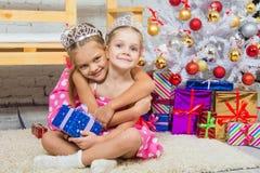 Flicka som kramar ett annat flickasammanträde på ett mattt på julgranen royaltyfri bild