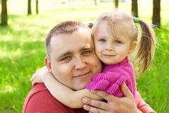 Flicka som kramar henne fader fotografering för bildbyråer