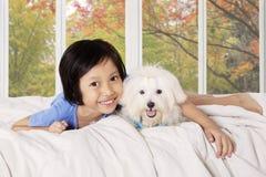 Flicka som kramar hennes valp på sängen Royaltyfria Bilder