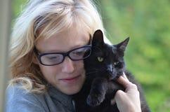 Flicka som kramar katten royaltyfri bild