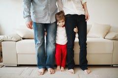 Flicka som kramar mamman och farsan för ben Arkivbild