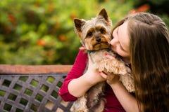 Flicka som kramar med hennes hund arkivfoton