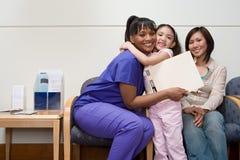 Flicka som kramar sjuksköterskan royaltyfri bild