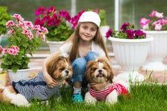 Flicka som kramar två hundkapplöpning på gräsmattan på en bakgrund av blommor arkivbild