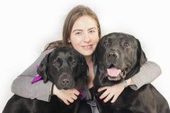Flicka som kramar två svarta labradors Arkivbilder