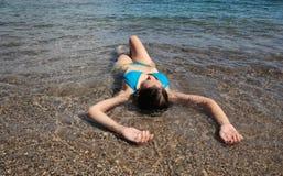 Flicka som kyler på strand 011 Royaltyfri Foto