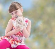 Flicka som kysser en kanin royaltyfria bilder