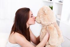 Flicka som kysser henne nallebjörn Arkivfoton