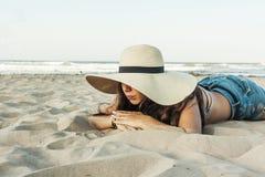 Flicka som läggas på för strandsommar för strand den bärande hatten Arkivbild