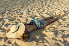 Flicka som läggas på för strandsommar för strand den bärande hatten Royaltyfria Bilder