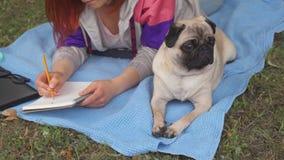 Flicka som lägger på en gräsmatta och en handstil, hennes mops som beside lägger lager videofilmer