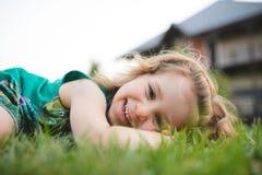 Flicka som lägger på gräs i gård Royaltyfri Foto