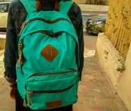 Flicka som lämnar för skola på nedgångmorgon, med påsen på baksida Royaltyfri Foto