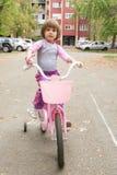 Flicka som lär att rida hennes cykel Arkivbilder