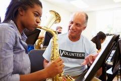 Flicka som lär att spela saxofonen i högstadiumorkester Arkivfoton