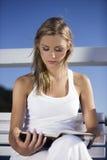 Flicka som läser en bok Arkivfoto