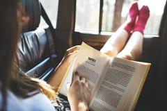 Flicka som läser en bok i en bil arkivbilder