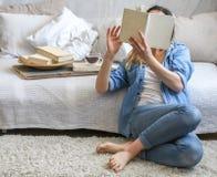 Flicka som läser en bok i ett hemtrevligt rum arkivfoto