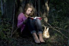 Flicka som läser en bok i skogen Royaltyfri Fotografi