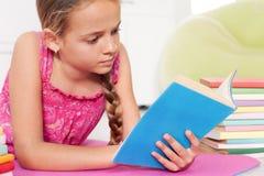 Flicka som läser en bok på golvet Fotografering för Bildbyråer