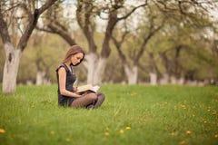Flicka som läser en bok på grön gräsmatta arkivbild