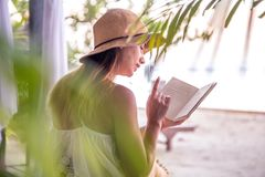 Flicka som läser en bok på stranden arkivfoto