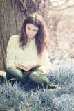 Flicka som läser en bok under ett träd Arkivfoton